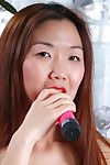 Asian chick Heidi Ho in sneakers fills her shaved pussy with pink vibrator on the floor
